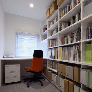 Inredning av ett modernt litet hemmabibliotek, med vita väggar, heltäckningsmatta, ett inbyggt skrivbord och grått golv