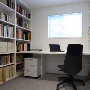 Bild på ett litet funkis hemmabibliotek, med vita väggar, heltäckningsmatta, ett inbyggt skrivbord och grått golv