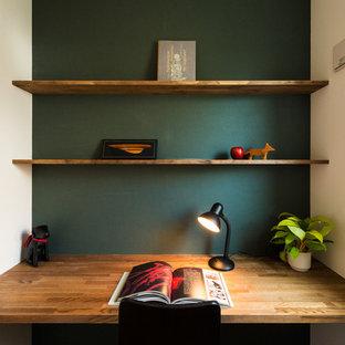 Immagine di un piccolo ufficio scandinavo con scrivania incassata, pareti verdi e nessun camino