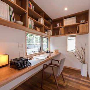 Создайте стильный интерьер: кабинет в восточном стиле с белыми стенами, паркетным полом среднего тона, встроенным рабочим столом и коричневым полом - последний тренд