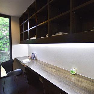 他の地域のモダンスタイルのおしゃれなホームオフィス・書斎 (白い壁、合板フローリング、暖炉なし、造り付け机、黒い床) の写真