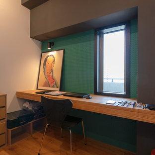 東京23区のコンテンポラリースタイルのおしゃれなホームオフィス・書斎 (緑の壁、無垢フローリング、造り付け机、茶色い床) の写真