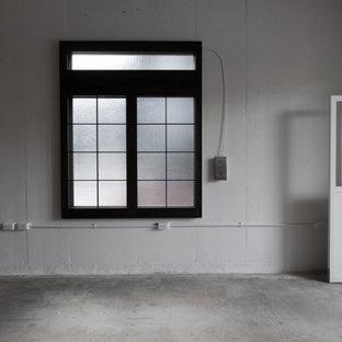 Réalisation d'un grand bureau atelier urbain avec un mur blanc, béton au sol et un sol turquoise.