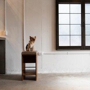 Aménagement d'un grand bureau atelier industriel avec un mur blanc, béton au sol et un sol turquoise.