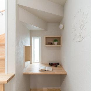 東京23区の小さい北欧スタイルのおしゃれなホームオフィス・書斎 (白い壁、無垢フローリング、造り付け机、茶色い床) の写真