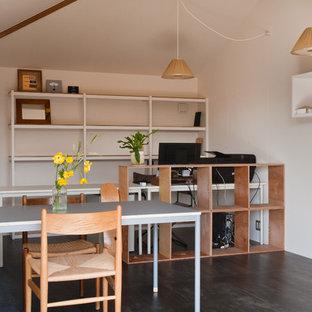На фото: кабинет в скандинавском стиле с белыми стенами, деревянным полом, отдельно стоящим рабочим столом и черным полом с