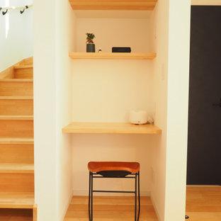 Foto på ett litet funkis hemmabibliotek, med vita väggar, ljust trägolv, ett inbyggt skrivbord och beiget golv