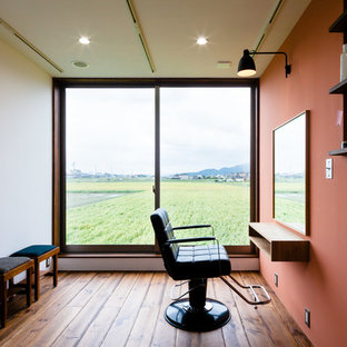 Example of a mid-sized built-in desk dark wood floor and brown floor home studio design in Other with red walls