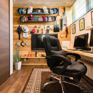 Asian built-in desk dark wood floor and brown floor home office photo in Other with brown walls