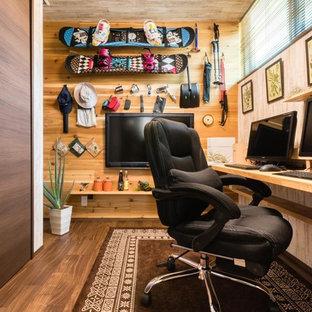他の地域のアジアンスタイルのおしゃれなホームオフィス・書斎 (茶色い壁、濃色無垢フローリング、造り付け机、茶色い床) の写真