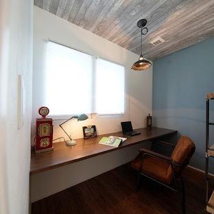 他の地域のビーチスタイルのおしゃれなホームオフィス・仕事部屋 (マルチカラーの壁、濃色無垢フローリング、茶色い床、造り付け机) の写真