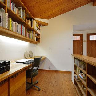 Foto di uno studio stile americano con pareti bianche, pavimento in legno massello medio, scrivania incassata e pavimento marrone