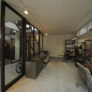 東京23区の小さいモダンスタイルのおしゃれなホームオフィス・仕事部屋 (白い壁、コンクリートの床、自立型机、グレーの床) の写真