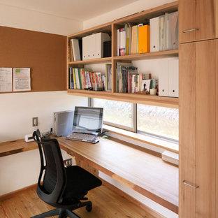 Стильный дизайн: маленький кабинет в восточном стиле с паркетным полом среднего тона, встроенным рабочим столом и коричневым полом - последний тренд