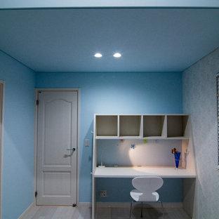他の地域のモダンスタイルのおしゃれなホームオフィス・書斎 (青い壁、塗装フローリング、自立型机、グレーの床) の写真