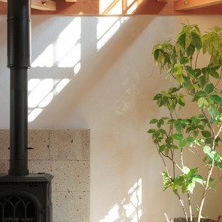 Modelo de estudio campestre con paredes blancas, escritorio independiente, estufa de leña y marco de chimenea de piedra