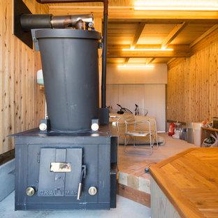 他の地域の中サイズのカントリー風おしゃれなクラフトルーム (茶色い壁、コンクリートの床、薪ストーブ、木材の暖炉まわり、自立型机、グレーの床) の写真