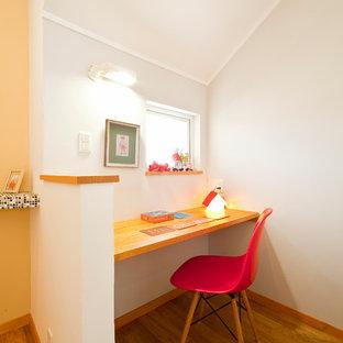 Inspiration pour un petit bureau nordique avec un mur blanc, un sol en bois brun et un bureau intégré.