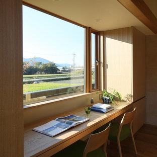 他の地域のアジアンスタイルのおしゃれなホームオフィス・仕事部屋 (ベージュの壁、無垢フローリング、造り付け机、茶色い床) の写真