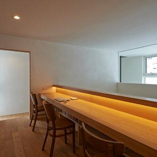 アジアンスタイルのおしゃれなホームオフィス・書斎 (ライブラリー、白い壁、淡色無垢フローリング、造り付け机、ベージュの床) の写真