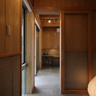 На фото: рабочее место среднего размера в скандинавском стиле с бежевыми стенами, бетонным полом, печью-буржуйкой, фасадом камина из бетона, встроенным рабочим столом и серым полом с