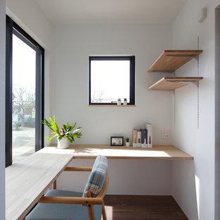 Modelo de despacho moderno, pequeño, con paredes blancas, suelo de madera oscura, escritorio empotrado y suelo marrón