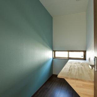 Exempel på ett litet modernt hemmabibliotek, med blå väggar, målat trägolv, ett inbyggt skrivbord och brunt golv