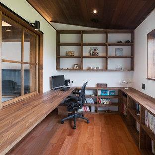 Ispirazione per uno studio etnico con pareti bianche, pavimento in legno massello medio, scrivania incassata e pavimento marrone