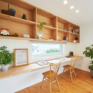 Cette image montre un bureau nordique de taille moyenne avec un mur blanc, un sol en bois clair et un sol multicolore.