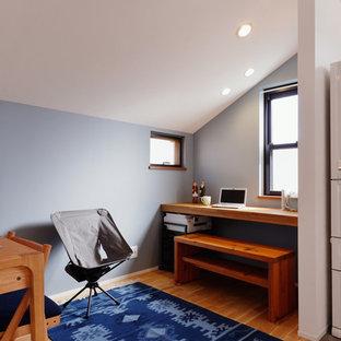 東京23区の小さいコンテンポラリースタイルのおしゃれなホームオフィス・仕事部屋 (青い壁、無垢フローリング、造り付け机、茶色い床) の写真