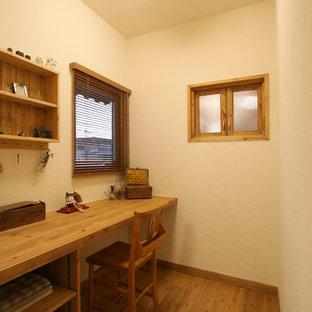 他の地域の地中海スタイルのおしゃれなホームオフィス・書斎 (白い壁、無垢フローリング、造り付け机、茶色い床) の写真