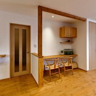 他の地域の北欧スタイルのおしゃれなホームオフィス・書斎 (白い壁、無垢フローリング、造り付け机、茶色い床) の写真
