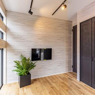 Idéer för att renovera ett mellanstort hemmabibliotek, med beige väggar, ljust trägolv och beiget golv