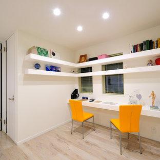 他の地域のモダンスタイルのおしゃれなホームオフィス・書斎 (白い壁、塗装フローリング、造り付け机、ベージュの床) の写真