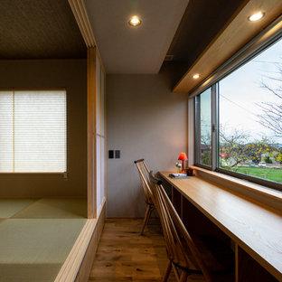 他の地域のアジアンスタイルのおしゃれなホームオフィス・書斎 (グレーの壁、無垢フローリング、造り付け机、茶色い床) の写真