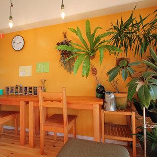 横浜のトロピカルスタイルのおしゃれなホームオフィス・仕事部屋 (オレンジの壁、無垢フローリング、自立型机、茶色い床) の写真