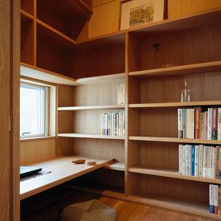 Bild på ett litet orientaliskt hemmabibliotek, med bruna väggar, ljust trägolv och ett inbyggt skrivbord