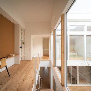 他の地域の北欧スタイルのおしゃれなホームオフィス・仕事部屋 (ライブラリー、白い壁、淡色無垢フローリング、造り付け机、茶色い床) の写真