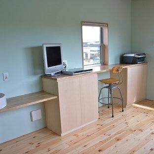 他の地域の中サイズのモダンスタイルのおしゃれなホームオフィス・仕事部屋 (緑の壁、淡色無垢フローリング、造り付け机、ベージュの床) の写真