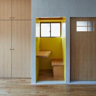 Bild på ett funkis hemmabibliotek, med gula väggar, mellanmörkt trägolv, ett inbyggt skrivbord och brunt golv
