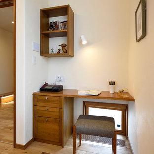 Kleines Asiatisches Arbeitszimmer ohne Kamin mit Arbeitsplatz, weißer Wandfarbe, braunem Holzboden, Einbau-Schreibtisch und braunem Boden in Sonstige