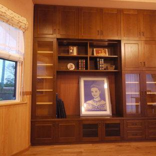 Bild på ett vintage arbetsrum, med ett bibliotek, bruna väggar, ljust trägolv, ett inbyggt skrivbord och brunt golv