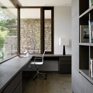 他の地域のモダンスタイルのおしゃれなホームオフィス・仕事部屋 (白い壁、塗装フローリング、造り付け机、グレーの床) の写真
