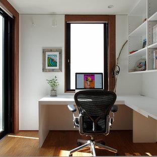 東京23区の中サイズのモダンスタイルのおしゃれな書斎 (白い壁、濃色無垢フローリング、造り付け机、茶色い床) の写真