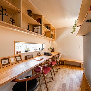 Skandinavisches Arbeitszimmer mit grauer Wandfarbe, braunem Holzboden, Einbau-Schreibtisch und braunem Boden in Sonstige