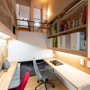 Пример оригинального дизайна: маленький кабинет в восточном стиле с белыми стенами, светлым паркетным полом, встроенным рабочим столом и коричневым полом