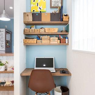Cette image montre un bureau nordique avec un mur multicolore, un sol en bois brun, un bureau intégré et un sol marron.
