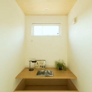 Ejemplo de despacho nórdico, pequeño, con paredes blancas, tatami, escritorio empotrado y suelo verde