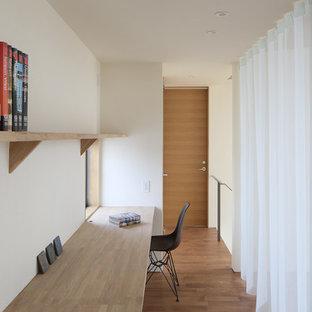 他の地域のモダンスタイルのおしゃれなホームオフィス・仕事部屋 (白い壁、無垢フローリング、造り付け机、茶色い床) の写真