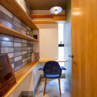 小さいモダンスタイルのおしゃれなホームオフィス・書斎 (マルチカラーの壁、造り付け机、グレーの床) の写真